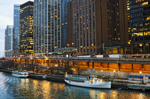 East Wacker Drive at night. The docked boats are mostly for architecture tours and there's a pedestrian walkway known as the Chicago Riverwalk. Source: Jonathan via Flickr Creative Commons