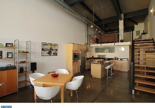 The industrial condo features 15-foot ceilings, exposed brick, steel beams and polished concrete floors.