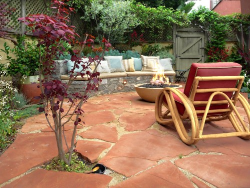 A burgundy-leafed tree and red cushions complement this  flagstone patio by Urban Oasis.