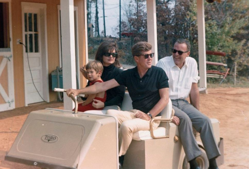 """President John F. Kennedy sits in a golf cart with family and friends at the Kennedy family residence, Wexford, in Atoka, Virginia. Left to right: John F. Kennedy, Jr.; First Lady Jacqueline Kennedy; President Kennedy (wearing sunglasses); Kennedy family friend, Kirk LeMoyne """"Lem"""" Billings. Source: http://www.jfklibrary.org"""