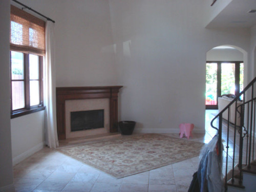 """Before: The living room's short fireplace and mantle appeared to be """"stuck on the wall."""""""