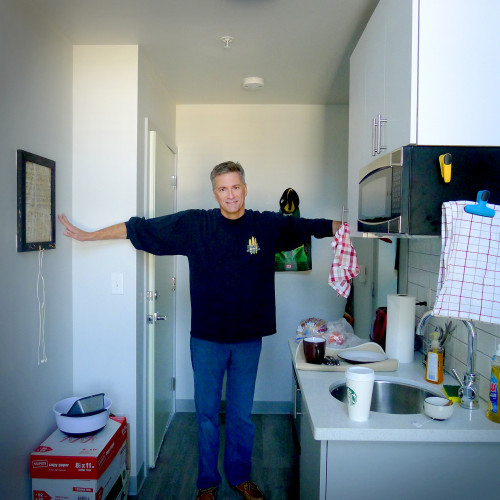 Peter in apartment with arms extended
