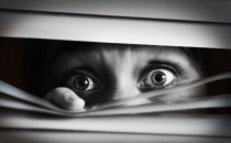 Scared woman peering through blinds