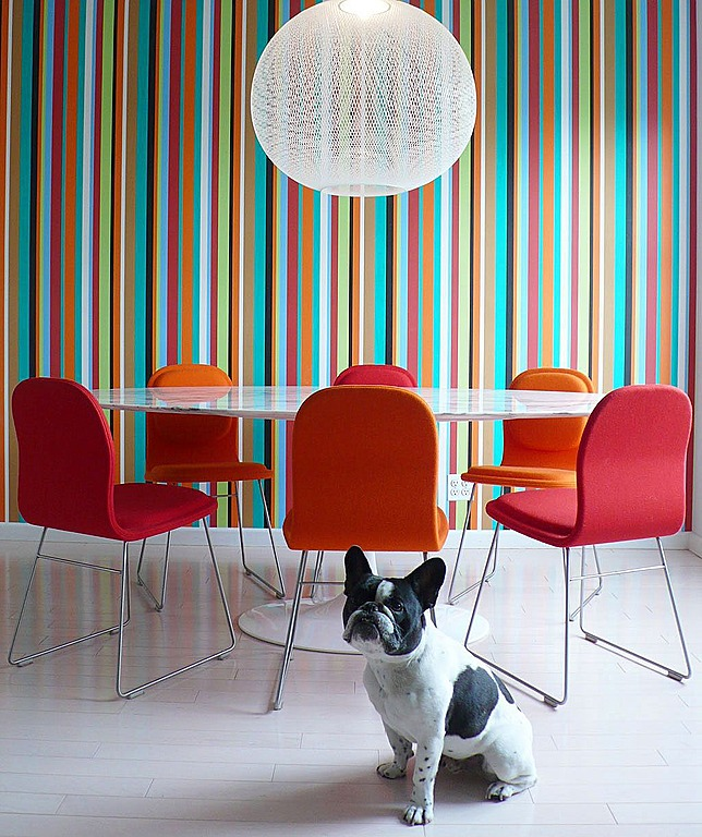 A white table and orange chairs balance the rainbow of colors in the wallpaper. By Alex Mundi Design